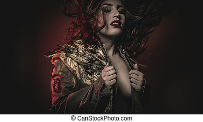 beautiful brunette woman with hair flying jacket and gold feathers