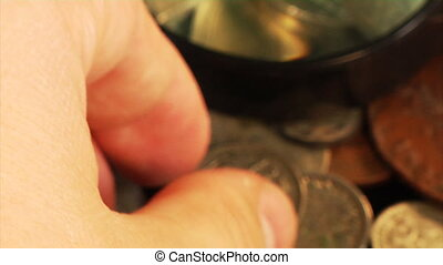 examining an old coin - close-up view examining an old...