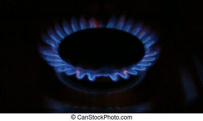 Gas burner on-off - A gas stove with blue flames in the...