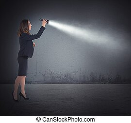 Torch lights to search - Businesswoman with a torch lights...