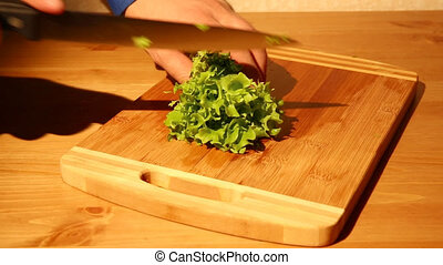 Cutting lettuce on a cutting board with a knife in a kitchen...