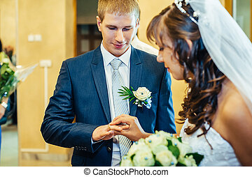 The groom puts on ring a hand to the bride - The groom puts...