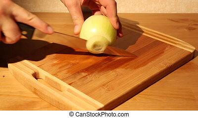Cutting an onion on a cutting board with a knife in a...