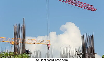 view of operating crane engine pulling hook against clouds -...