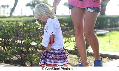 blonde girl in Ukrainian walks along parapet taking moms...
