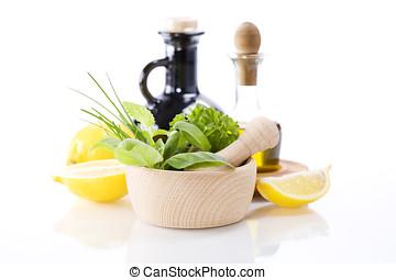 Olive oil, vinegar, Healing herbs and lemon over white