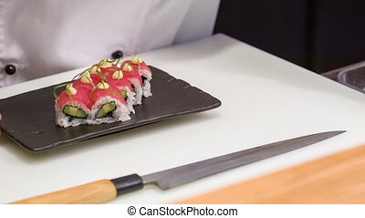 Asian chef giving last touch for sushi rolls adding to it...