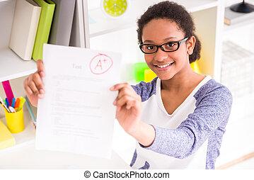 Schoolgirl showing test results - Young mulatto schoolgirl...