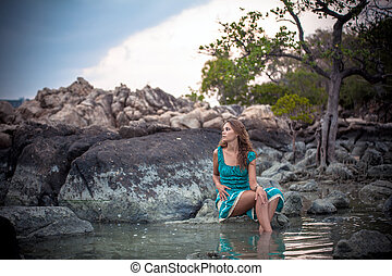 Young beautiful woman in long turquoise dress sitting on a...