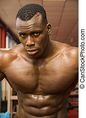 Hunky muscular black bodybuilder working out in gym, resting...