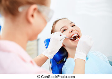 Visiting dentist - Young female sitting at the dentist and...