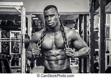 Attractive hunky black male bodybuilder posing with iron...