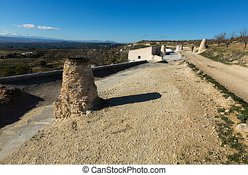 Stovepipe of dwelling caves built into rock. Cortes de Baza,...