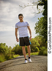 Handsome young man walking and trekking on road in the...