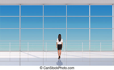 Businesslady standing back in front of window Interior view