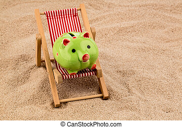 deckchair with piggy bank on the sandy beach symbol photo...