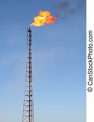 Gas flare with fire on blue sky background