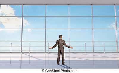 Businessman throwing up his hands in front of big window,...
