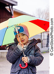 child with umbrella, a symbol of childhood