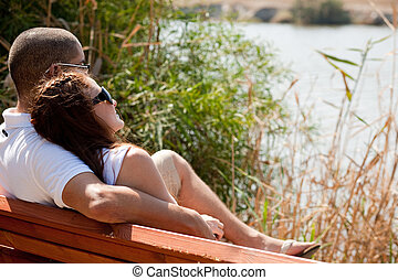 Couple sitting at the wooden bench