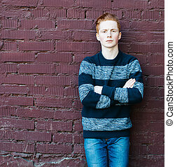 Young redhead man in a sweater and jeans standing next to a...
