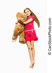 cute girl lying on floor and hugging big teddy bear -...