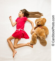 smiling girl lying on floor and pretending to run fast with...