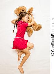 girl in pink dress sleeping on big teddy bear on floor -...