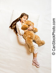 Isolated photo of cute sleeping girl hugging teddy bear -...