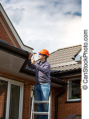 carpenter standing on high ladder and repairing house roof -...