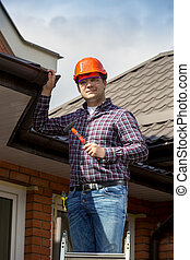 smiling repairman standing on high ladder at sunny day -...