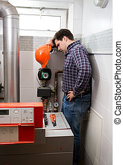 Plumber with hard hat looking at complicated heating system...