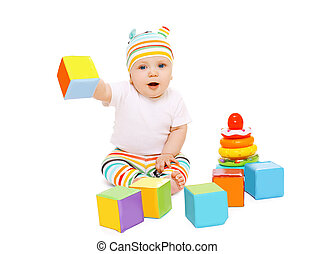 Funny baby in striped hat playing with colorful toys