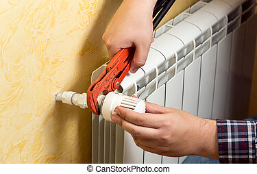 Closeup of man installing heating radiator and connecting...
