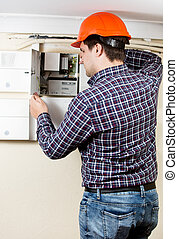 electrician installing components in electrical shield