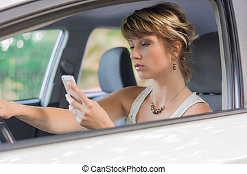 Young woman using mobile phone while driving a car -...