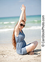 Woman raising her hands doing exercises on the beach sand