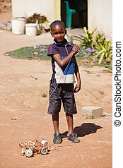 African child - small African boy , outdoors, playing with a...