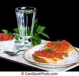 Aperitif - Sandwiches with red caviar and glass of vodka on...