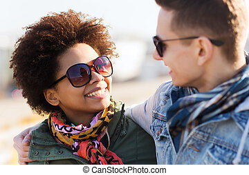 happy teenage friends in shades talking outdoors -...