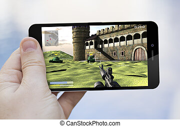 using cell phone to play - gaming concept: hand holding a 3d...