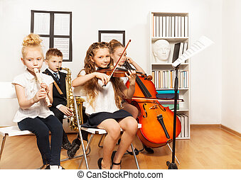 Cheerful children playing musical instruments together in...