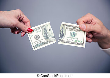 Concept image of a female and male hand dividing money over...