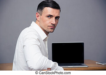 Businessman sitting at thet able with blank laptop screen -...