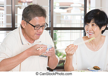 Asian Senior Couple Eating Meal At Home Family living...