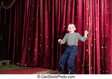 Exuberant little boy performing on stage at a pantomime...