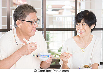 Senior Couple Eating Meal At Home Asian family living...