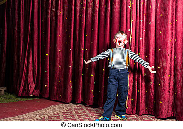Adorable little boy singing on stage during a play standing...