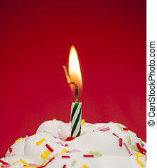 Cupcake with a lit candle over red background