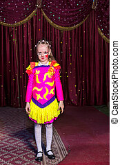 Adorable little girl in a pink and yellow costume with her...